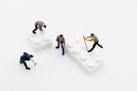 Miniature people: Worker digging white box. Service,  repair and  maintenance concept. Reklamní fotografie - 133559759