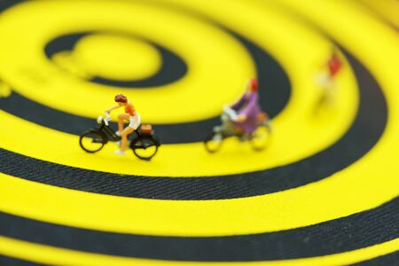 Miniature people ride bicycles on yellow dart boards.
