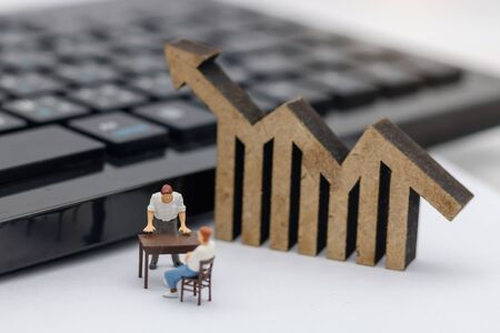 Miniature people sitting on table with keyboard and wooden graph.