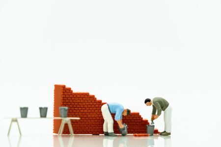 Miniature people: Worker fix the wall before the world. Concepts of finding a solution, problem solving and challenge. 版權商用圖片