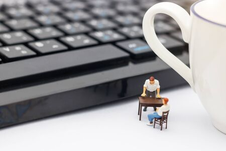 Miniature people sitting on table with keyboard and cup of coffee. Reklamní fotografie - 133560002