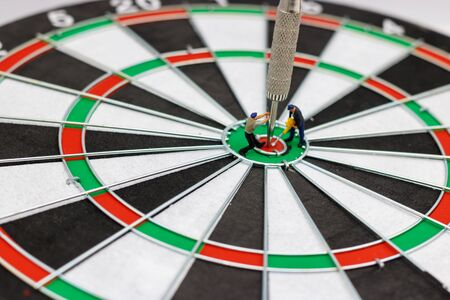 Miniature people digging the arrow in the middle of the target to the dart board. Concept of doing for goals.