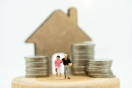 Mainature people standing with coins stack and home.  Home financial investment Concept. Reklamní fotografie - 133560003
