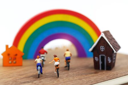 Miniature people enjoy riding a bicycle with home and rainbow. 版權商用圖片