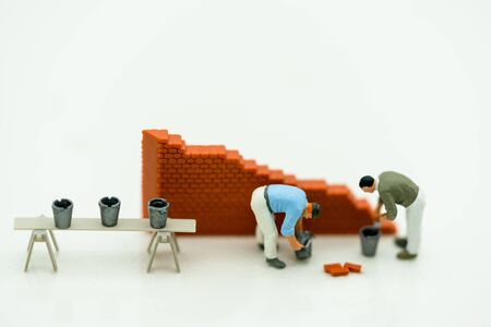 Miniature people: Worker fix the wall before the world. Concepts of finding a solution, problem solving and challenge. Reklamní fotografie - 133560062