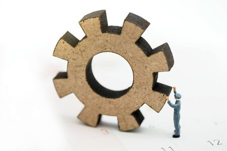 Miniature people with gear cog symbol on calendar, Business management and working process concept.