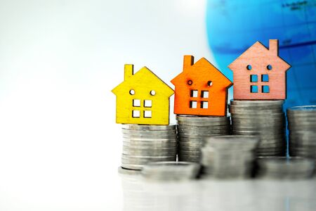 Mainature people standing with coins stack and home.  Home financial investment Concept. 版權商用圖片