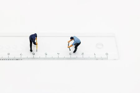 Miniature people: Worker digging white ruler. Service,  repair and  maintenance concept.