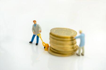 Miniature people: Worker transportation golden coin. Reklamní fotografie - 133560070