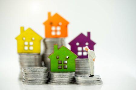 Mainature personnes debout avec pile de pièces et maison. Accueil investissement financier Concept. Banque d'images