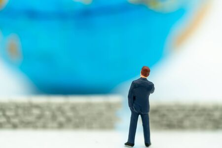 Miniature people: Businessman standing with wall and world. Concepts of finding a solution, problem solving and challenge.