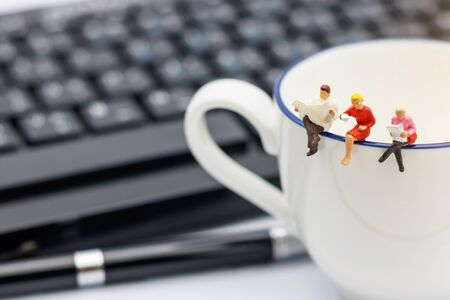Miniature people sitting on cup of coffee with keyboard and pen.