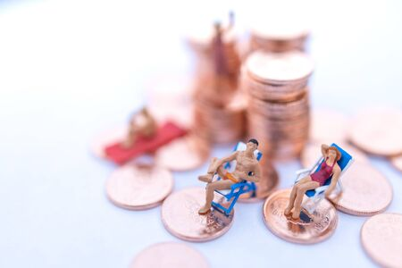 Miniature people sitting on beach sunbath seats and  coins stack. Summer concept