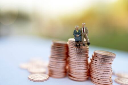 Miniature people: Happy old people sitting on coins stack, Retirement  and Life insurance Concept.