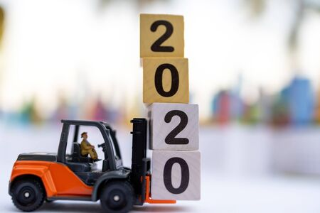 Miniature people: The delivery service of loader with number 2020 on wooden box. Concepts of logistics and transportation. 版權商用圖片