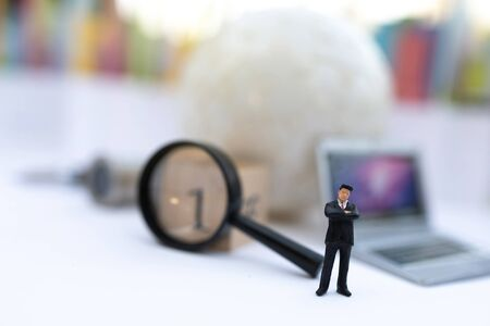 Miniature people: Businessman with white globe and laptop, use a magnifying glass to get number one. Recruitment finding employee and business concept.