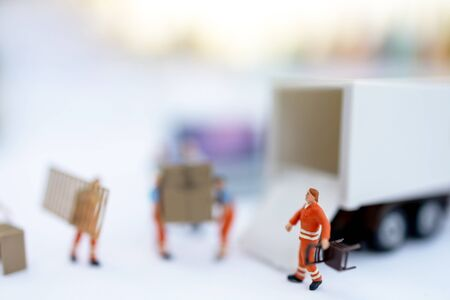 Miniature people: The delivery service of loader. Concepts of logistics and transportation
