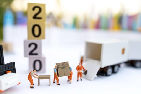 Miniature people: The delivery service of loader with number 2020 on wooden box. Concepts of logistics and transportation. Stock fotó