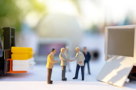 Miniature people handshake for the delivery service of loader. Concepts of logistics and transportation.