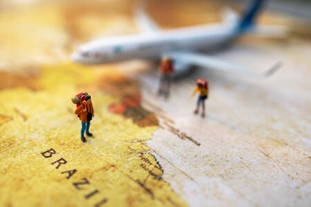 Minature people: traveling with a backpack standing on vintage world map and plane,  Travel and vacation concept.
