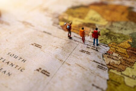 Minature people: traveling with a backpack standing on vintage world map, Travel and vacation concept.