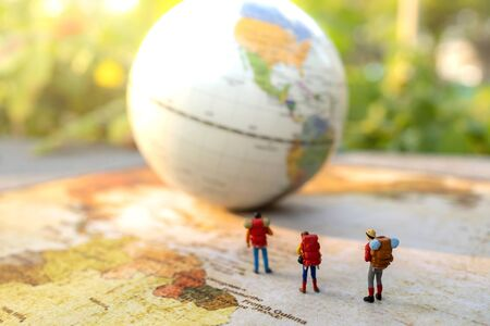 Miniature people: traveling with a backpack standing on vintage world map and globe,  Travel and vacation concept.