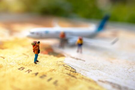 Miniature people: traveling with a backpack standing on vintage world map and plane,  Travel and vacation concept.