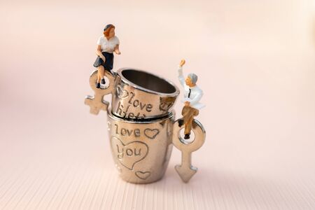 Miniature people Couple Lover sit on cup off coffee as pink background, lovely concept. 版權商用圖片