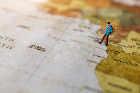 Miniature people: traveling with a backpack standing on vintage world map, Travel and vacation concept. Reklamní fotografie