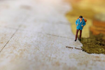 Miniature people: traveling with a backpack standing on vintage world map, Travel and vacation concept. 版權商用圖片