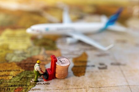 Miniature people:  Worker loading coins  to plane. Shipping and online delivery service concept.