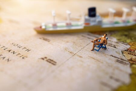 Miniature people sit on beach sunbath seats on Vintage World Map and ship, Summer Concept.