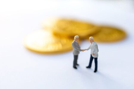 Miniature people:  Businessmen handshake with gold coins, Growth in business concept. 版權商用圖片