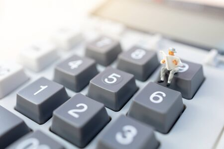 Miniature people: Businessman reading on calculator. Financial and business concept Reklamní fotografie