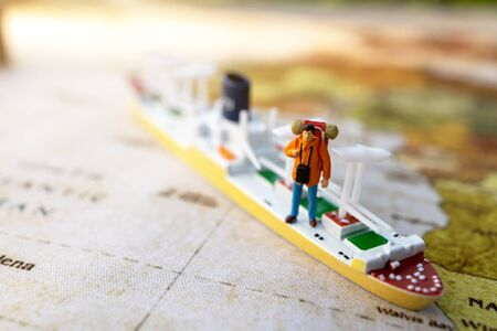 Minature people: traveling with a backpack standing on vintage world map and ship,  Travel and vacation concept.