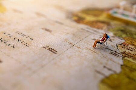 Miniature people sit on beach sunbath seats on Vintage World Map, Summer Concept.