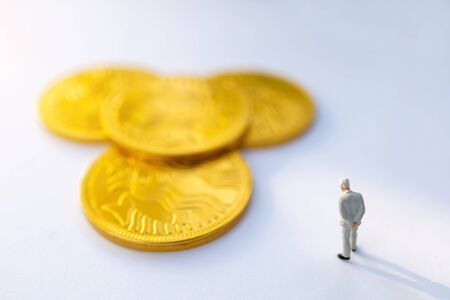Miniature people:  Businessman stand and think about gold coins, Growth in business concept.