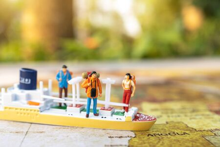 Miniature people: traveling with a backpack standing on vintage world map and ship,  Travel and vacation concept.