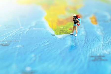 Minature people: traveling with a backpack standing on world map, Travel and summer concept.
