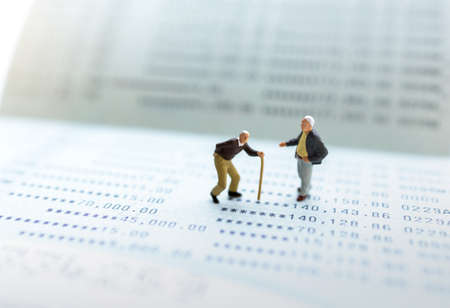 Miniature people stand on the bank passbook, Retirement planning and life insurance concepts. Reklamní fotografie