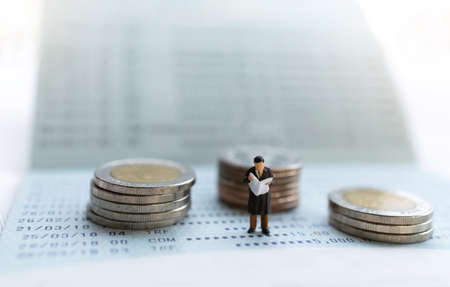 Miniature people stand on the bank passbook and coins stack, Retirement planning and life insurance concepts.