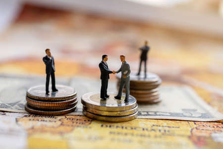 Miniature people: Businessman handshake with coins stack on world map,  Investment, agreement, partnership and business concept