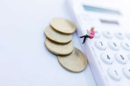 Miniature people: Businessman reading a book with coins and sitting on the calculator and calendar. Education or business concept.