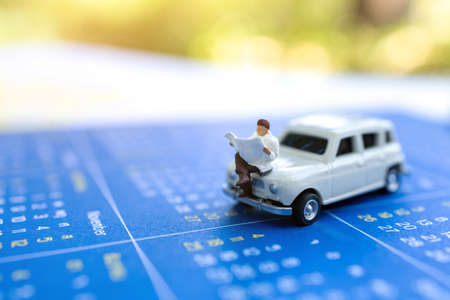 Miniature people: Businessman reading on car and calendar, education or business concept. Reklamní fotografie