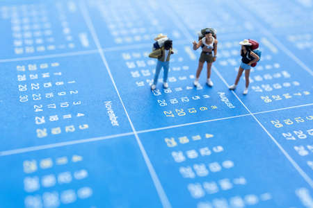 Miniature people: Traveler with a backpack standing on calendar, Travel and vacation Concepts.