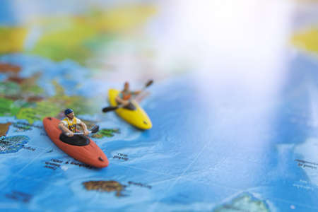 Miniature people: Traveler sitting on board canoe and world map. Travel, vacation and  summer concept.