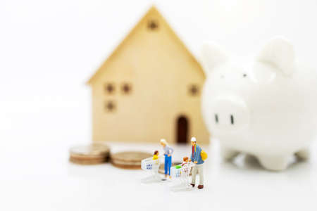 Miniature people: Parent and children standing with home and piggy bank , Home purchase planning and money saving concept.