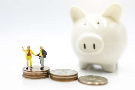 Miniature people: Elderly person standing on coins stack with piggy bank, Retirement planning concept.
