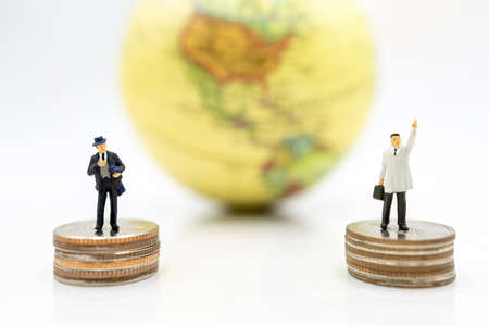 Miniature people: Businessman standing on coins stack with globe. Finance and business concept. Stock Photo