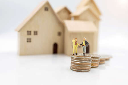 Miniature people: Elderly person standing on coins stack with home, Retirement planning concept.